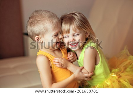 older brother hagging his younger sister, smiling siblings - stock photo