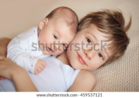 older brother hugging newborn baby