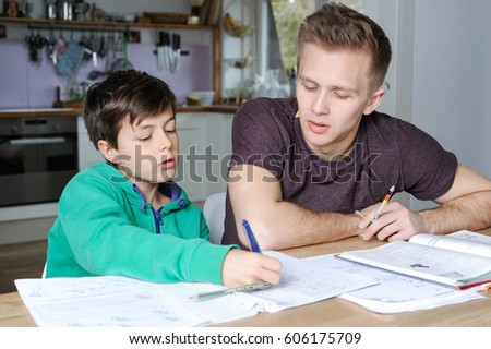 Older brother is helping his little brother with his maths homework