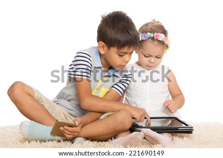 Older brother teaches younger sister play on a tablet PC. Children six and two years.  - stock photo