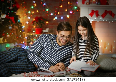 Older brother with little sister reading books and eating cookies in Christmas living room - stock photo