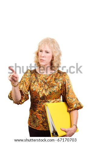 older business woman holding a book or ledger and pointing to something  with a quizzical look - stock photo