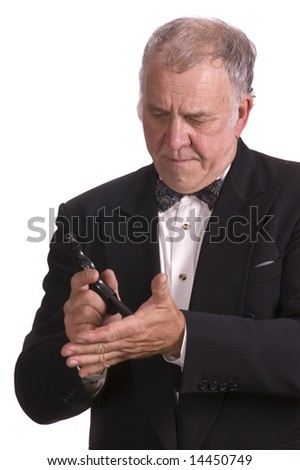 older businessman in a suit impersonating James Bond isolated on white with a gun