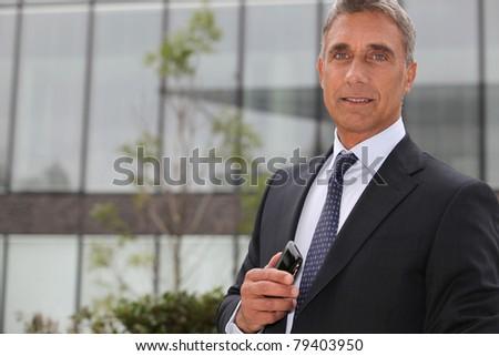 Older businessman using a cellphone - stock photo
