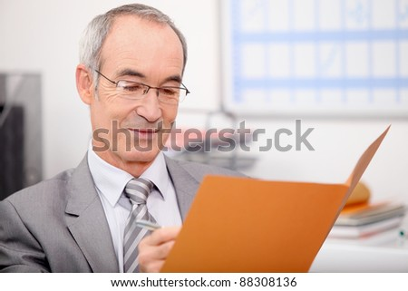 Older businessman writing in a file - stock photo