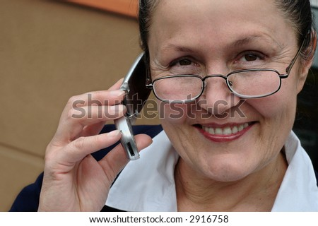 Older businesswoman making a transaction on the phone - stock photo