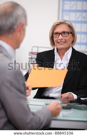 Older businesswoman with a colleague - stock photo