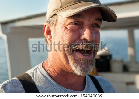 Older, caucasian, bearded Lobster fisherman talking and looking off to the side, Maine, USA - stock photo
