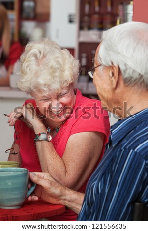 Older Caucasian woman laughing at table with man - stock photo