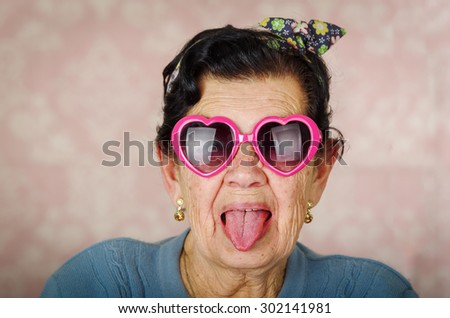 Older cool hispanic woman wearing blue sweater, flower pattern bow on head and pink heartshaped sunglasses looking into camera showing her tongue. - stock photo