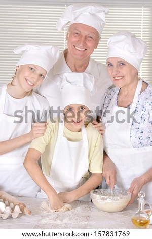 older couple and their grandchildren knead the dough for biscuits together - stock photo