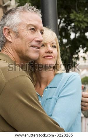 Older couple cuddling outside - stock photo