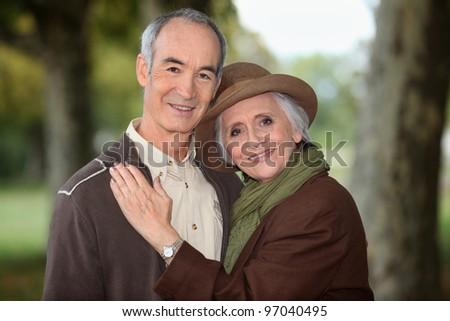 Older couple enjoying an autumnal stroll - stock photo