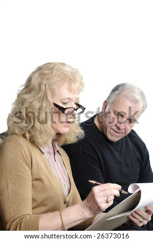 older couple going over their monthly expenses to determine what risk they have at losing their home during this economic crisis and the damage the stock market has had on their investments - stock photo
