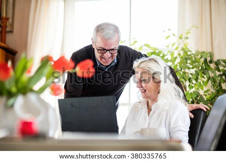 Older couple having fun and smiling while working from home on notebook with green flowers and window light around them - stock photo