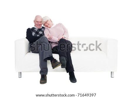 Older couple in a sofa isolated on white background - stock photo