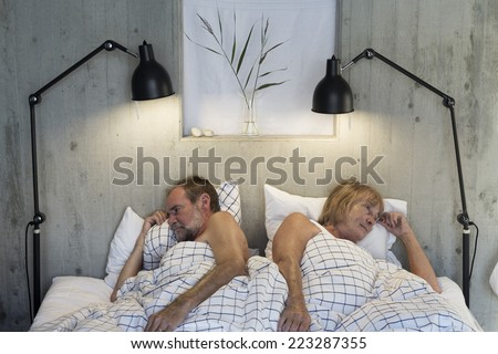 Older couple in bed angry - stock photo