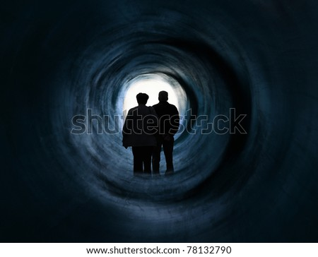 Older couple in front of white light tunnel end. it May symbolise escape, looking for exit or freedom and even death or clinical death. Psychedelic vision.