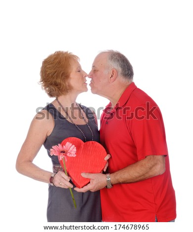 Older couple kissing as a sign of affection or love isolated on white - stock photo