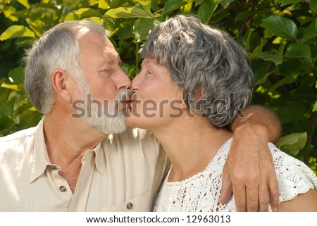 Older couple kissing in the park on a warm summer day
