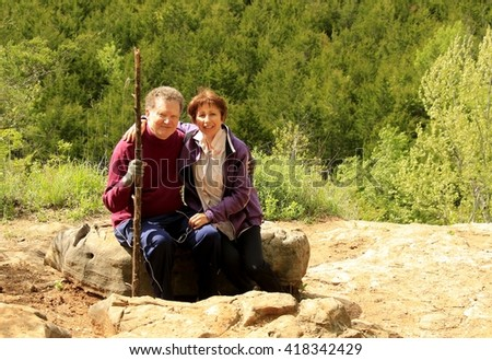 Older couple resting on a high bluff above the creek below; dense forest on the other side of the creek - stock photo