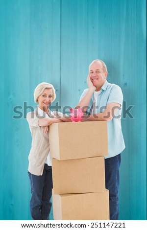 Older couple smiling at camera with moving boxes and piggy bank against wooden planks background - stock photo