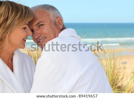 Older couple smooching in the sand dunes - stock photo