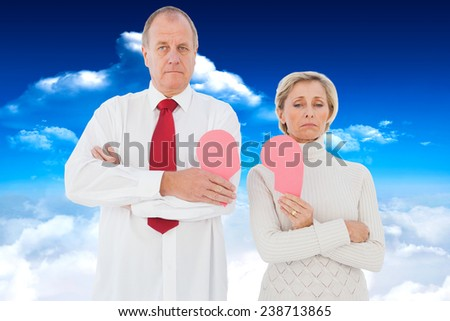 Older couple standing holding broken pink heart against bright blue sky with clouds - stock photo