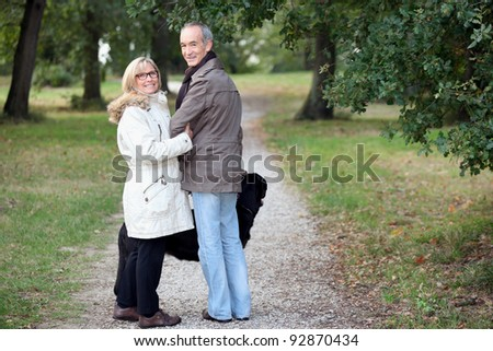 Older couple strolling through a park - stock photo