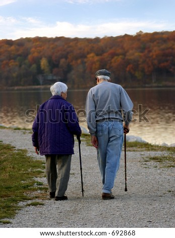 Older couple walking along edge of pond in autumn