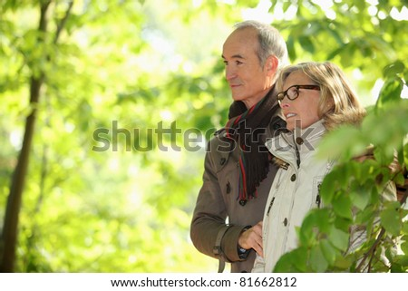 Older couple walking in the woods - stock photo