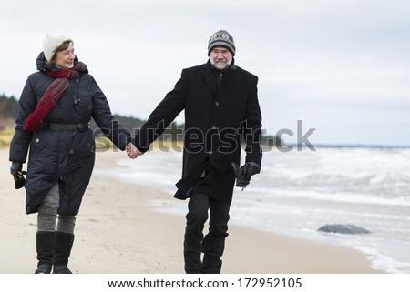 Older couple walking the beach - stock photo
