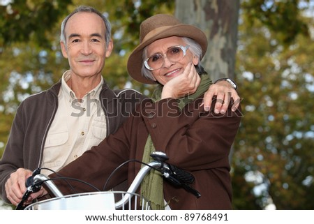 Older couple with a bicycle - stock photo