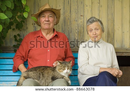 Older couple with cat sit outdoors - stock photo