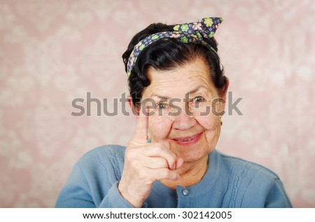 Older cute hispanic woman wearing blue sweater and flower pattern bow on head holding up one finger for the camera in front of pink wallpaper. - stock photo