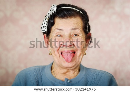 Older cute hispanic woman wearing blue sweater and polka dot bowtie on head showing her tongue to the camera in front of pink wallpaper. - stock photo