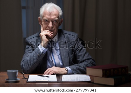 Older elegant man thinking in his vintage study room - stock photo