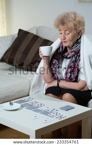 Older elegant woman drinking cup of hot tea - stock photo