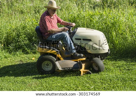 Older farmer cutting grass with a straw hat on.