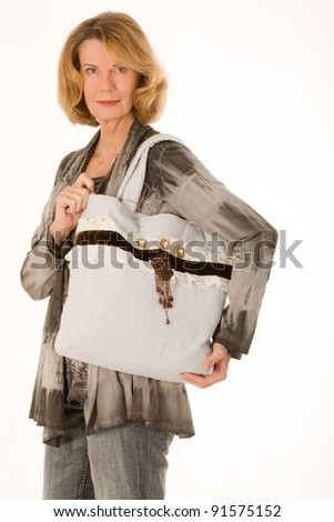 older fashionably dressed woman with designer bag made ??of fabric /older woman with fashionable shopping bags - stock photo