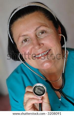 Older, friendly nurse holding a stethoscope - stock photo