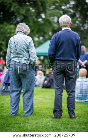 Older generation, seniors, enjoying an outdoors music, culture, community event, festival.