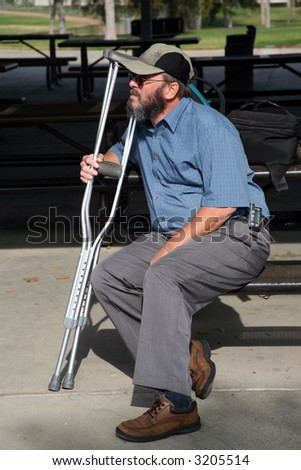 Older gentleman resting on a park bench while holding his crutches and contemplating his accident - stock photo