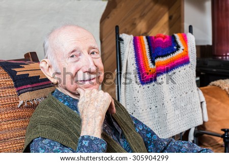 Older gentleman smiling and seated in his living-room - stock photo