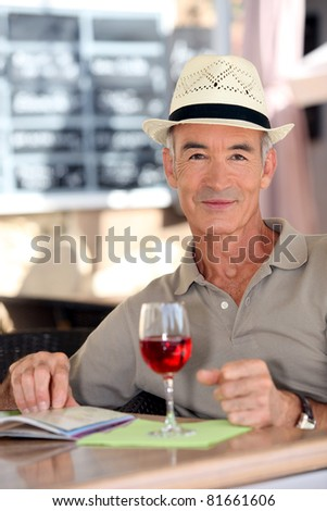Older gentleman tourist drinking a glass of rose in a restaurant - stock photo
