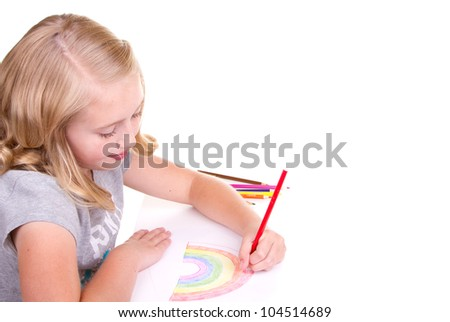 Older girl or teen drawing a rainbow with colored pencils - stock photo