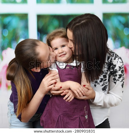 Older girls kiss their little sister - Family, childcare and love concept - stock photo