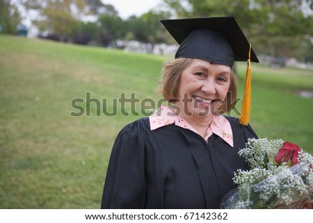 Older graduate holding flower bouquet