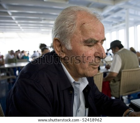 Older Greek man traveling on a boat - stock photo