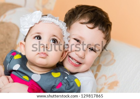 Older happy brother holding cute newborn baby sister - stock photo